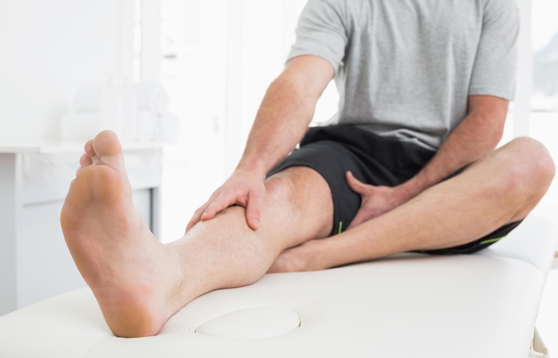 Man holding elevated leg pain